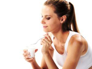 Женщина пьет йогурт