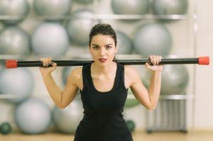 Девушка делает упражнения с гимнастической палкой