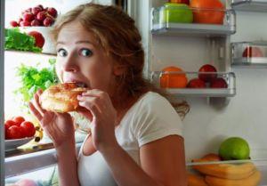 Девушка ест на ночь у холодильника