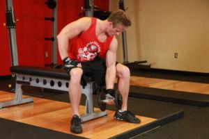 Спортсмен выполняет концентрированные подъемы гантелей с супинацией