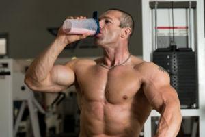Мужчина принимает протеин перед тренировкой