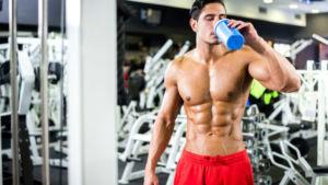 Спортсмен принимает протеин во время тренировки