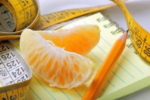 Записная книжка и мандарин