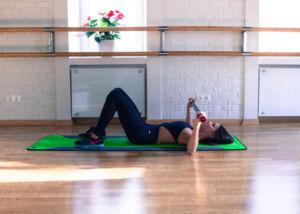 Девушка делает упражнения с гимнастической палкой лежа