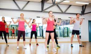 Девушки делают упражнения с гимнастической палкой